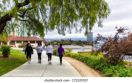 OAKLAND,CA-JAN.11,2014:People on the newly paved 3.4 mile pedestrian path around Lake Merritt in downtown Oakland.The lake was recently renovated, adding new parks and an amphitheater.