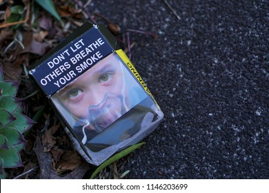 Oakleigh, VIC / Australia - July 31 2018: Empty Australian cigarette pack on street with warning don't let others breathe your smoke