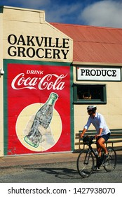 Oakville, CA, USA August 21, 2013 A bicycler pedals past the Oakville Grocery Store with a large cola advertisement, in the Oakville California