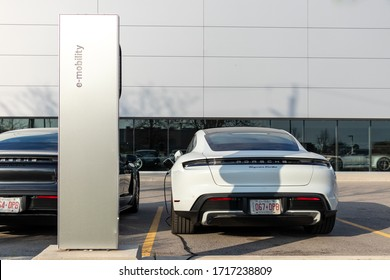 OAKVILLE, CANADA - April 18, 2020: Porsche e-mobility EV charging station at a dealership with two new Porsche Taycan's in the background.