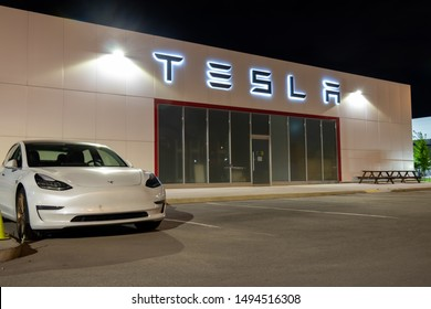 OAKVILLE, CANADA - August 31, 2019: Tesla logo at a Tesla Dealership  illuminated at night and a Tesla Model 3 parked beside.