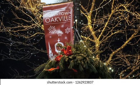 OAKVILLE CANADA - DEC 1 2018: Downtown Oakville sign above a hanging Christmas basket with red ribbon at night with holiday lights on trees in the background