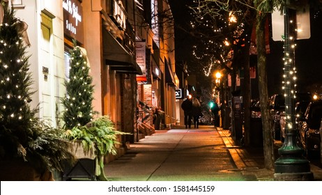 OAKVILLE CANADA - DEC 1 2018: Well-lit sidewalk in downtown Oakville at night with festive lights on trees for the holiday season