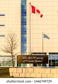Oakville, Ontario, Canada - April 29, 2018: Sign and flag at Ford Motor Company of Canada in Oakville, Ontario, Canada.  The Ford Motor Company is an American multinational automaker.