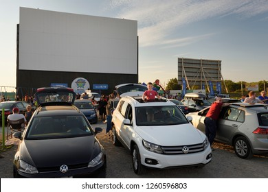Oakville, Ontario, Canada - August 16, 2017: Standing boy looking out sunroof at Volkswagen drive in movie theatre event in Oakville Canada at sundown