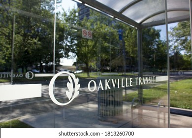 Oakville, Ontario / Canada - September 11, 2020: Oakville transit logo on the transparent glass of a shelter at the bus stop in a green residential neighbourhood.
