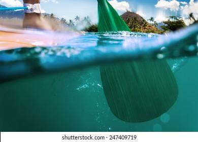 Oar of paddle boarder half way submerged in ocean water paddling
