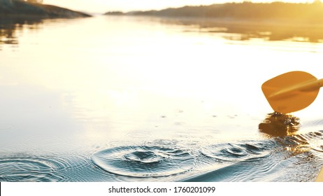 oar paddles on calm water against the background of sunset rays, outdoor activities on a kayak, water sports