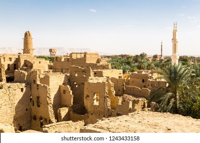 Oasis with ruins of ancient middle eastern Arab town built of mud bricks, old mosque with minaret. New city in background. Al Qasr, Dakhla Oasis, Western Desert, New Valley Governorate, Egypt, Africa.