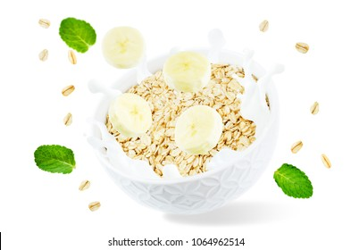 Oat bowl with splash of milk and flying banana slices isolated