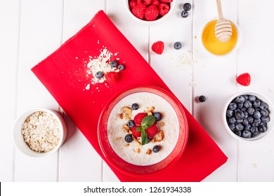 Oat Cereal Breakfast in Red Bowl with Rasperry. Blueberry and Honey in Yogurt Cooked Fiber Cereal Flake Porridge Healthy Morning Food. Oatmeal Muesli Ingredient Healthy Lifestyle Top Down View