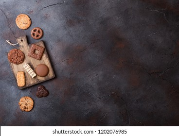 Oat and chocolate cookies selection on wooden board on stone kitchen background