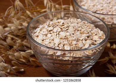 Oat ears stems and oat flakes in a bowl on a dark brown wood background. oat flakes big and small size grind. oatmeal flakes coarse. large-sized flakes. Useful fiber-rich product. close up.