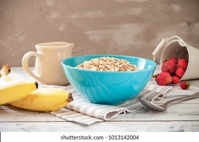 Oat flakes in a bowl with fruits ready to cook. Bananas, apples, strawberries, jug with milk and spoon on the light wooden table