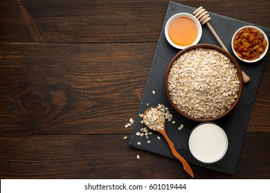 Oat flakes in the bowl and honey, raisins, milk on slate board and rustic wooden background. Oats bowl top view, copy space.