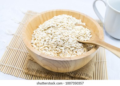 Oat flakes in bowl and wooden spoon isolated on white background. Healthy food.