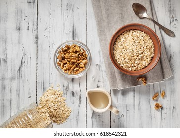 Oat flakes in brown clay bowl ready to cook, scattered oat flakes, walnuts, jug with milk and spoon on the light wooden table. View from above