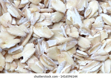 Oat flakes closeup as background, natural color, high contrast.