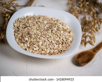 Oat flakes and ears of oats. Oatmeal in a plate on the table. Healthy breakfast