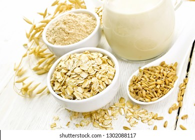 Oat flakes and flour in bowls, grain in a spoon, oatmeal milk in a glass jug and ripe oaten stalks on the background of a light wooden board