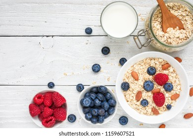 Oat flakes with fresh berries and nuts on a white wooden table. healthy breakfast. top view with copy space
