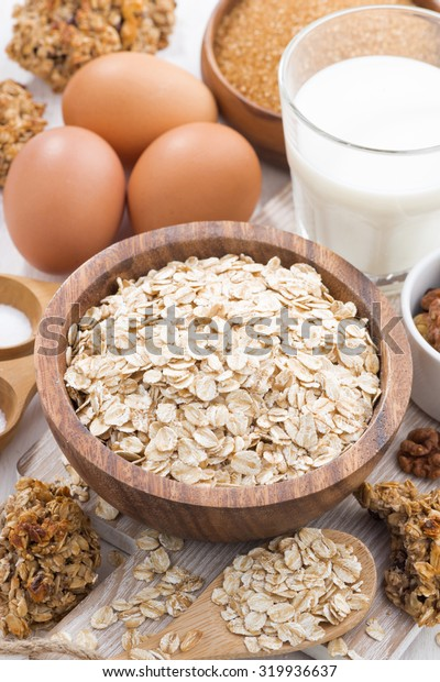 oat flakes and ingredients for making cookies on white table, vertical, close-up, top view