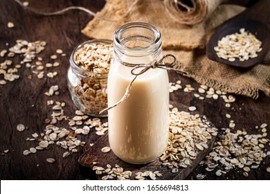 Oat flakes milk, non dairy alternative plant based drink in glass, wooden rustic kitchen table, copy space