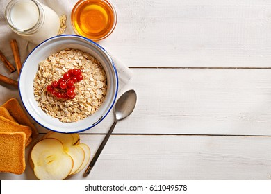 Oat flakes plate with honey, milk, apple, cinnamon, toast and currants on a wooden table. Top view of healthy oat flakes breakfast. Copy space