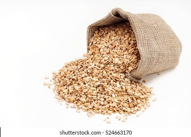 Oat flakes scattered from sack on white background. Copy space, high resolution product