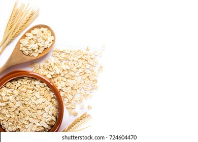 Oat flakes, uncooked oats in bowl with wooden spoon and wheat ears on white background. Concept of healthy eating, vegan food, healthy food, breakfast.