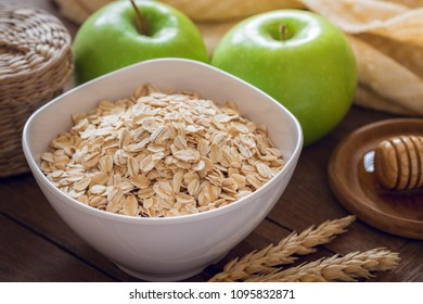 Oat flakes in white bowl with fresh green apple and honey