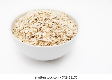 oat flakes in a white bowl on a white background