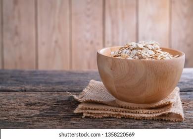 Oat flakes in wooden bowl on wooden table. Oatmeal, Oats - Food, Oat Flake.
