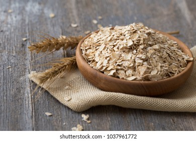 Oat flakes in wooden plate on rustic table. Natural organic food in vintage style concept.