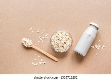 Oat milk alternative on beige background, copy space, top view. Healthy vegan substitute dairy free drink - bottle of oat milk.