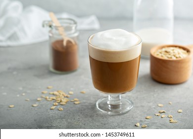 Oat milk latte with thick foam in a glass