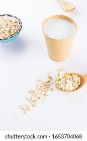 Oat milk. Organic oat milk in a paper cup. Healthy vegan non-dairy organic drink with oat flakes. Alternative milk. Zero waste