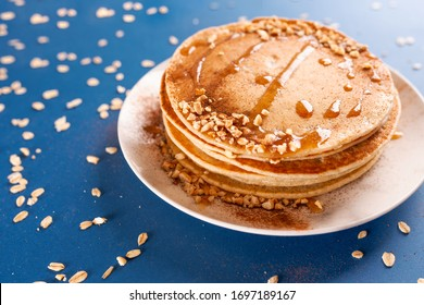 Oat pancakes on white dish with nuts and syrup, with oatmeal. Classic blue background. 2020
