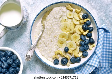 Oat porridge with banana, nuts  and fresh blueberry in a bowl on a light blue slate, stone or concrete background.Top view.