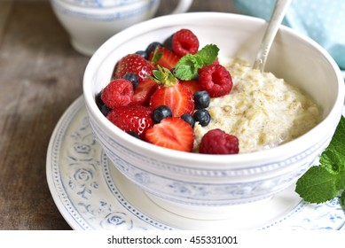 Oat porridge with fresh berries in a vintage bowl on a rustic wooden background.