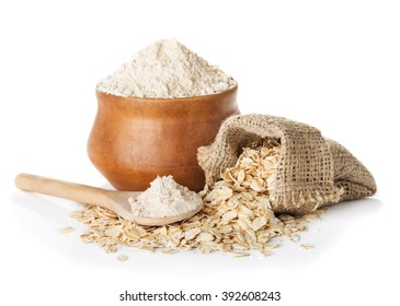 oat  wholegrain flour in bowl and  spoon,   bag with oat flakes isolated on a white background closeup
