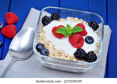 Oat with yogurt and berries in a bowl on wooden table