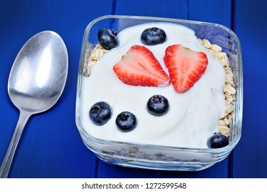 Oat with yogurt and fruits in a bowl on blue wooden table