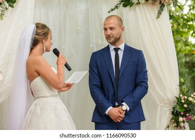 Oath of bride and groom at wedding ceremony on wedding arch background.
