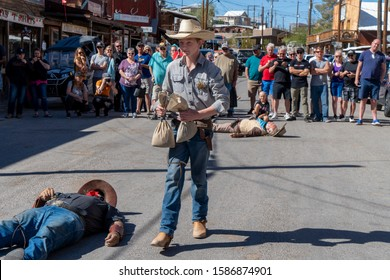 Oatman, Arizona / USA - 20 Oct 2019: The final stage of the famous gunfight and bank robbery enacted to entertain tourists to the town. The young sheriff takes the money while robbers lay dead.