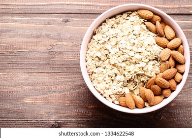Oatmeal with almonds in bowl on brown wooden table