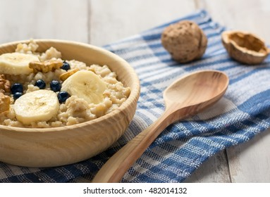 Oatmeal with bananas and blueberries on a checkered towel
