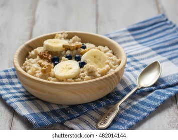 Oatmeal with bananas and spoon on the table
