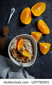 Oatmeal in to the bowl. with orange .selective focus