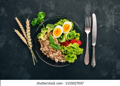 Oatmeal with chicken eggs, cherry tomatoes and vegetables. Healthy food. On a black stone table. Top view. Free space for text.